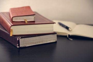 Auf dem Bild sieht man drei Bücher und ein Notizbuch